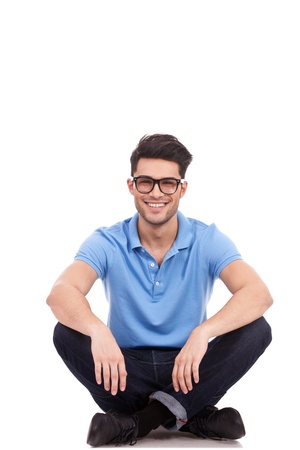 Photo for young casual man with eyeglasses sitting on the floor in the lotus position and smiling - Royalty Free Image