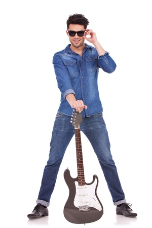 full length picture of a young casual man holding a guitar between his spread legs and holding his sunglasses