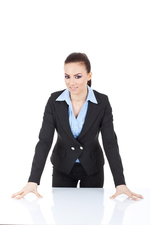 Photo pour young business woman standing in front of the desk, leaning on it and smiling at the camera. isolated on white - image libre de droit