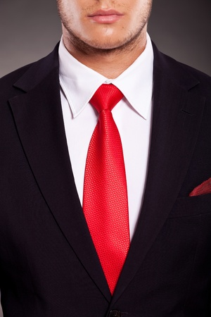 detail of young business man's suit with red tie, on dark background