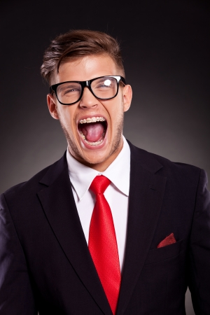 portrait of a young business man with eyeglasses shouting with mouth wide open, on dark background