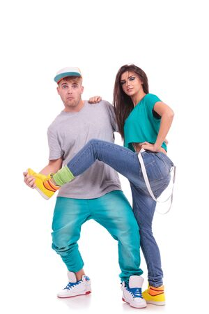 couple of young hip hop dancers fooling around. the man is holding the woman's leg and looking at the camera. isolated on white