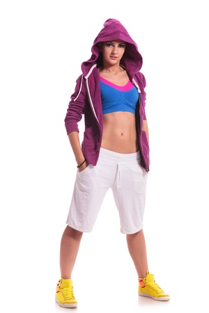 full length picture of a young sporty woman standing with her hands in her pockets and looking confident at the camera
