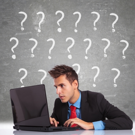 curious business man looking at laptop computer's screen and having lots of questions