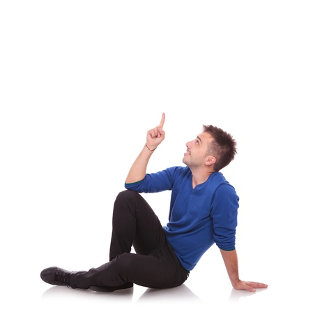 young casual man sitting on the floor, pointing and looking upwards while smiling. on white background