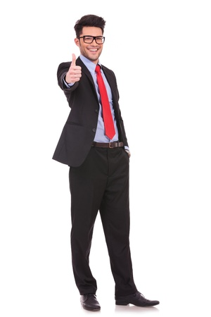 full length picture of a young business man showing thumb up and holding the other hand in his pocket, while smiling to the camera  on white background