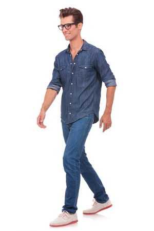 casual young man walking and looking forward, away from the camera, with a smile on his face. isolated on a white background