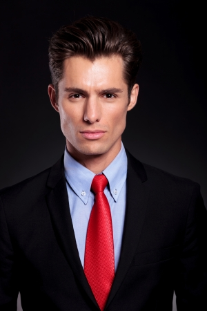 closeup portrait of a young business man standing against a black background and looking at the camera with seriousness