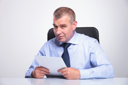 senior bussines man sitting at the desk with some papers in his hands and looking at the camera . on gray background