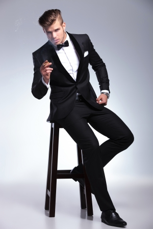 elegant young fashion man in tuxedo sitting on a stool and holding a cigar in his hand while looking at the camera. on gray background