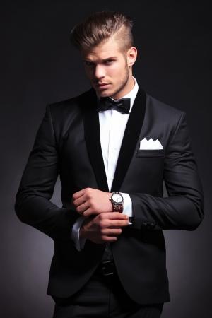 Foto de elegant young fashion man in tuxedo adjusting his cufflinks while looking at the camera. on black background - Imagen libre de derechos