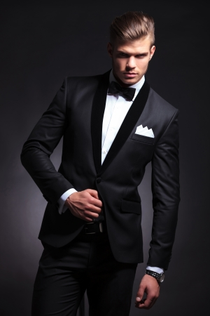 elegant young fashion man with a hand on his tuxedo jacket looking at the camera. on black background