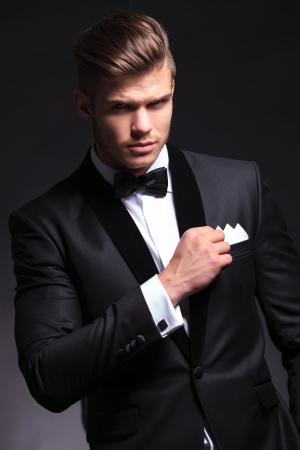 elegant young fashion man in tuxedo holding his pocket handkerchief with a hand while looking at the camera.on black background