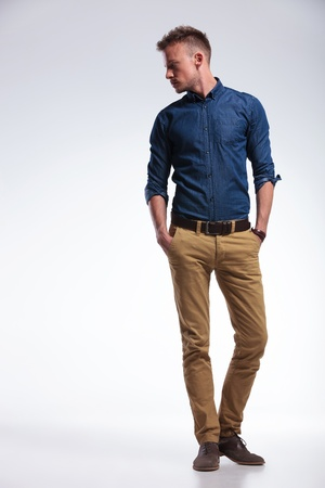 Foto de full length portrait of a casual young man standing with both hands in his pockets while looking to his side, away from the camera. on gray background - Imagen libre de derechos