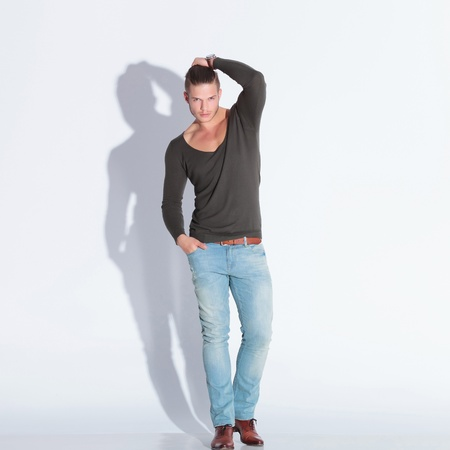 full body picture of a casual young man holding his hair while looking at the camera with a hand in his pocket. on gray studio background with shadow