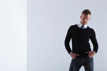 casual young man holding both hands in his pockets and looking into the camera. on light gray studio background