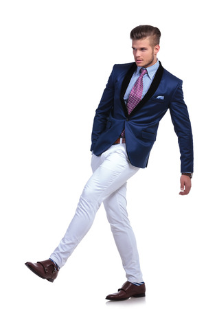 full length photo of a young business man pretending to kick something while holding a hand in his pocket and looking away from the camera. on a white background
