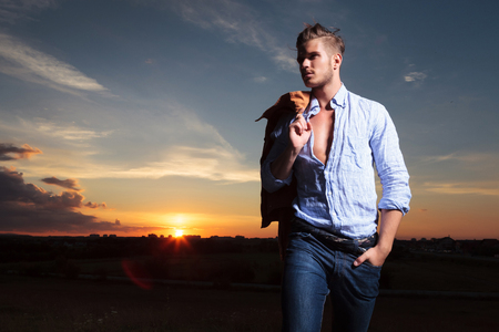 casual young man standing outdoor with a hand in his pocket and his jacket on his shoulder while looking away with the sunset behind