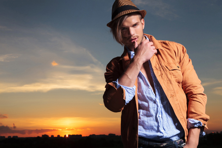 casual young man standing outdoor and looking down at the camera while touching his lower lip with his thumb and the sunset behind
