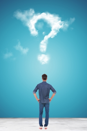 back of a Handsome casual young man looking at a big question mark made of clouds