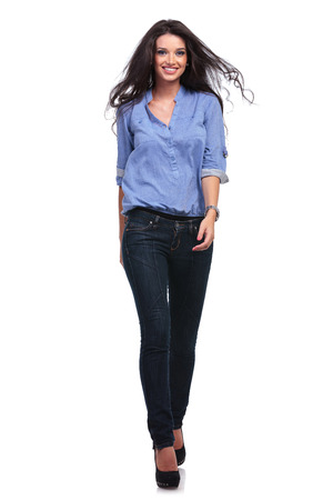 full length picture of a young casual woman walking toward the camera and smiling.