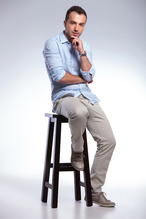 full length photo of a young casual man sitting on a chair and touching his chin while looking pensively at the camera. on gray background