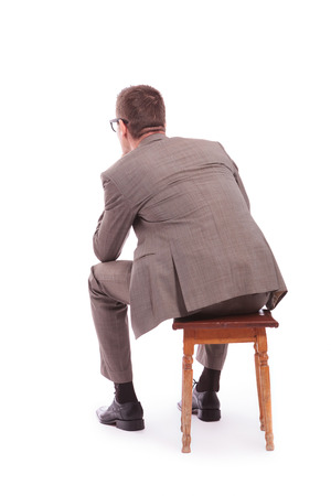back view of a young business man sitting on a chair. on a white background