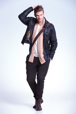 full body picture of a young fashion model passing his hand through his hair and smiling to the camera