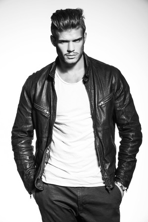 black and white picture of a young fashion model in leather jacket standing with his hands in his pockets