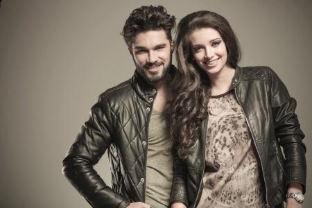 Foto de happy fashion couple in leather jackets smiling to the camera in studio - Imagen libre de derechos