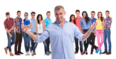 mature casual man welcoming to his young team of casual people on white background