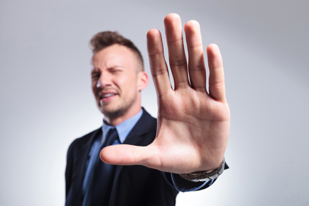 young business man stopping you with his hand. on a light gray studio background
