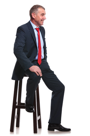 mid aged business man sitting on a chair and smiling away from the camera. isolated on a white