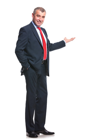 mid aged business man presenting something in the back while holding a hand in his pocket and smiling for the camera. isolated on a white