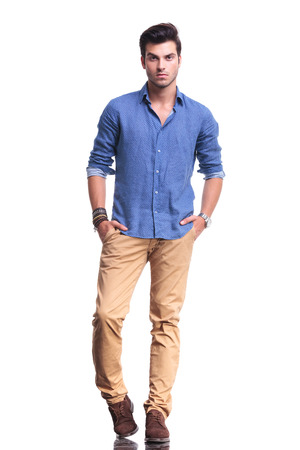 Photo pour full body picture of a young casual man with hands in his pockets on white background - image libre de droit