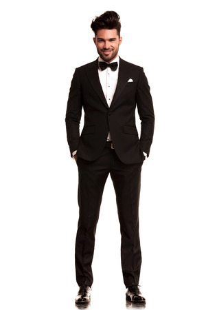 smiling young man wearing tuxedo standing with hands in pockets on white background