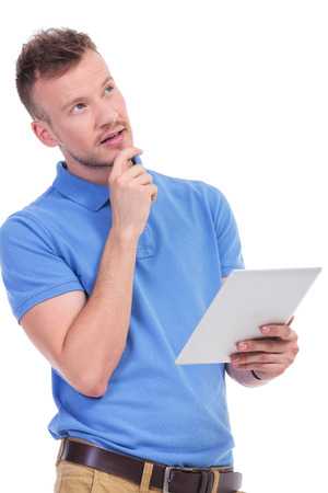 picture of a young casual man holding a tablet in a hand and looking away pensively with his other hand at his chin. isolated on a white background