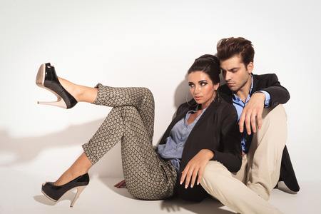 Photo for Fashion couple sitting on the floor together, looking away from the camera. The woman is leaning on ther man. - Royalty Free Image