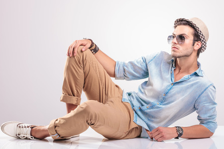 Foto de cool fashion man lying on the floor, holding one knee up, looking away from the camera. - Imagen libre de derechos