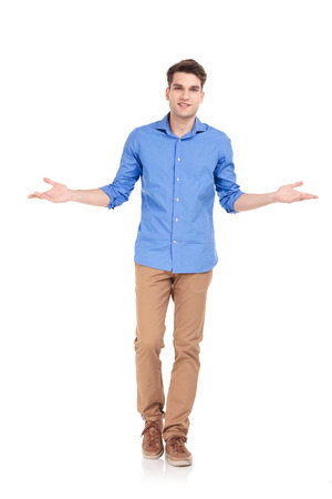 Photo pour Full body picture of a young casual man walking while welcoming you. - image libre de droit