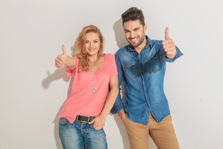 Photo pour Happy young couple leaning on a wall while showing the thumbs up gesture. - image libre de droit