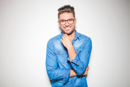 beautiful young man wearing glasses, smiling and touching his chin