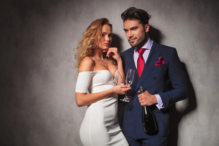 elegant couple ready to party with a botle of champagne in studio