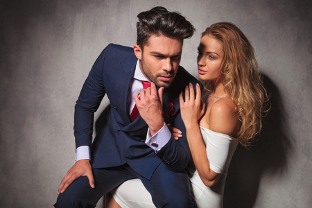 woman is looking at his elegant man while he is sitting on her lap, in studio