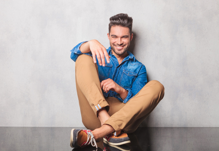 Foto de smiling man in denim shirt sitting legs crossed in studio background resting his arm on his leg - Imagen libre de derechos