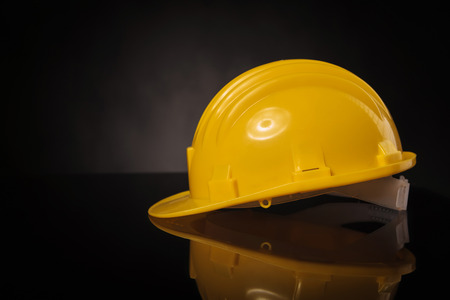 Photo pour side view of a yellow construction safety  helmet on a black table with reflexion - image libre de droit