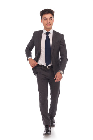 Foto de full body picture of a young business man walking and looking away from the camera on white studio background - Imagen libre de derechos