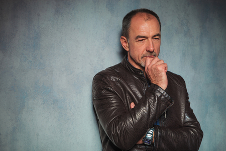 Photo pour portrait of handsome mature man in leather jacket standing and thinking in gray studio background while looking away from the camera - image libre de droit