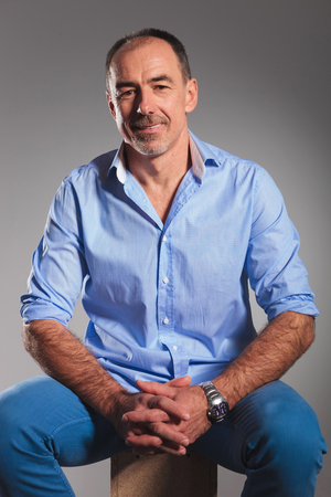 Photo pour closeup portrait of mature man in open blue shirt with hands together posing seated in gray studio background while looking at the camera - image libre de droit