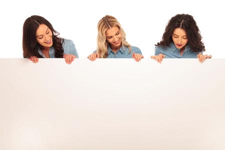Foto de three happy young casual women looking down to a big blank board on white background - Imagen libre de derechos